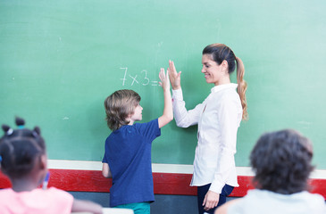 Teacher congratulating with kid in primary classroom