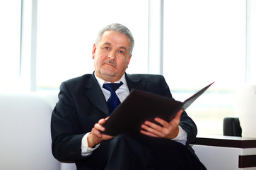 businessman in office with a folder sits and works