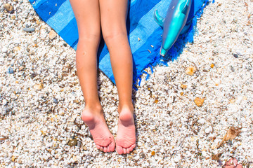 Closeup of little girl legs on tropical beach with pebbles