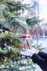 Beautiful red vintage Christmas lantern on warm mittens outdoors