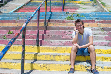 Young man with cellphone in old staircase