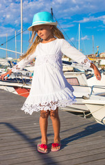 Cute little girl having fun in a port during summer vacation