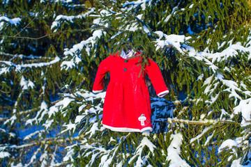 Kid's red Santa dress in a snowy fir forest