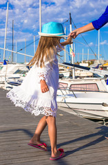 Adorable little girl have fun in a port on summer day