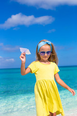 Little girl with paper airplane have fun on white sandy beach