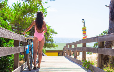Young beautiful woman in swimsuit walking with bicycle on a