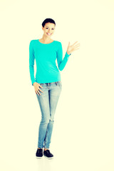 Young casual woman showing welcome gesture.