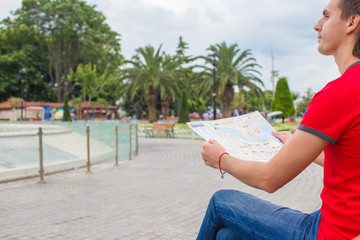 Man with city map on a trip while walking at summer vacation