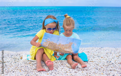 Adorable little girls with map of island on tropical beach © travnikovstudio