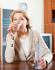mature woman sitting in the table and drinking fresh water