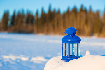 Blue lantern with a candle on white snow outdoor