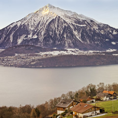 Panoramic view over Swiss Apls mountains near the Thun lake in w