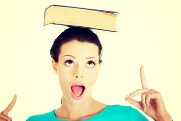 Beautiful woman with book on her head.