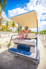 Dad and his little daughters driving golf cart on tropical beach