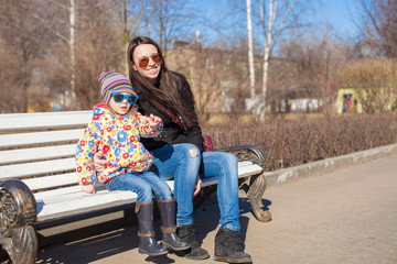 Little cute girl with her mother walking on sunny day outdoors