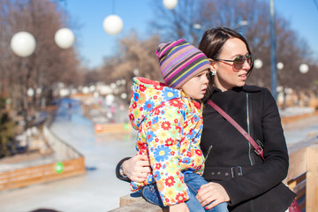 Little girl and mother walking on sunny day outdoors