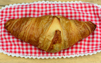 croissant on old wooden table and checkered doily