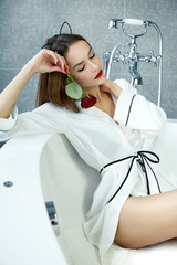 Sexy woman in bathroom in silk robe rose Valentine's day .