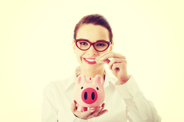 Business woman with coin and piggy- bank.