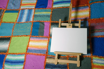 painting easel in front of a colorful handmade quilt