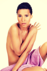 Attractive woman sitting covered with towel.