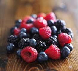 pile of fresh assorted berries on wooden table