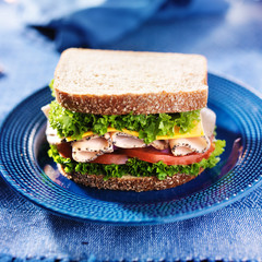 turkey deli meat sandwich on blue plate