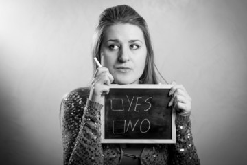 "Monochrome portrait of woman thinking on ""yes"" or ""no"" answer"