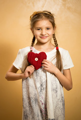 cute little girl holding decorative red heart