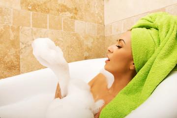 Side view woman blowing a foam, relaxing in bath