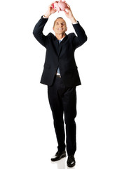Full length cheerful businessman holding piggybank