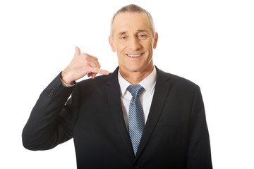 Portrait of businessman with call me gesture