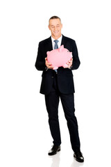 Full length cheerful businessman holding piggybank