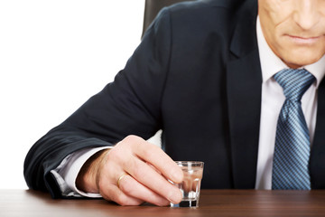 Overworked man drinking vodka in office