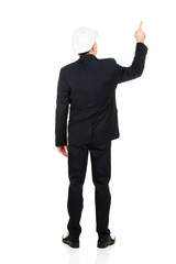 Businessman with hard hat pointing up