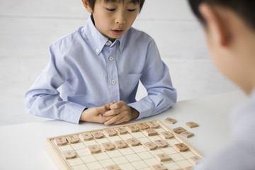 Boy seriously playing in Japanese Chess