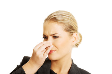 Woman pinching her nose because of disgusting smell