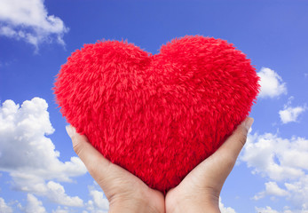 hand hold red heart on blue sky background