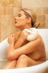Woman relaxing in a bath and washing herself