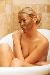 Woman sitting in bath with chocolate face mask