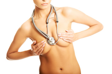 Nude woman with a stethoscope covering her breast
