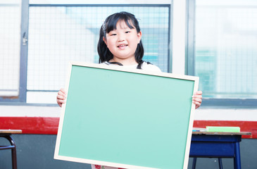 Asian female girl holding empty chalkboard in primary classroom
