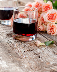 Glasses of Red Wine and Pink Roses on Wooden Background