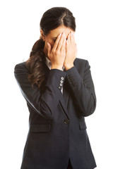 Businesswoman covering her face because of shame