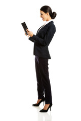 Full length happy businesswoman reading her notes