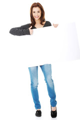 Young woman with blank billboard