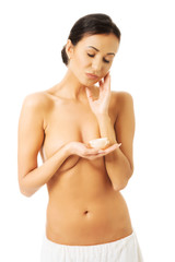 Portrait of a topless woman with cream container