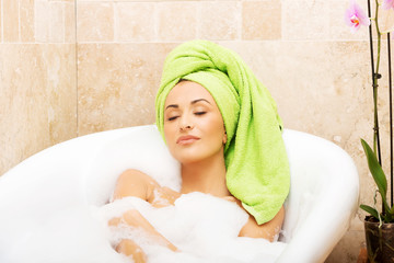 Woman relaxing in bath with eyes closed