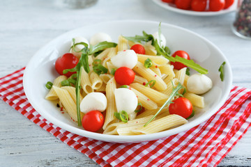 Pasta on a plate with cherry tomatoes and mozzarella cheese