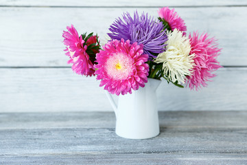 Bouquet of colorful asters in a white vase